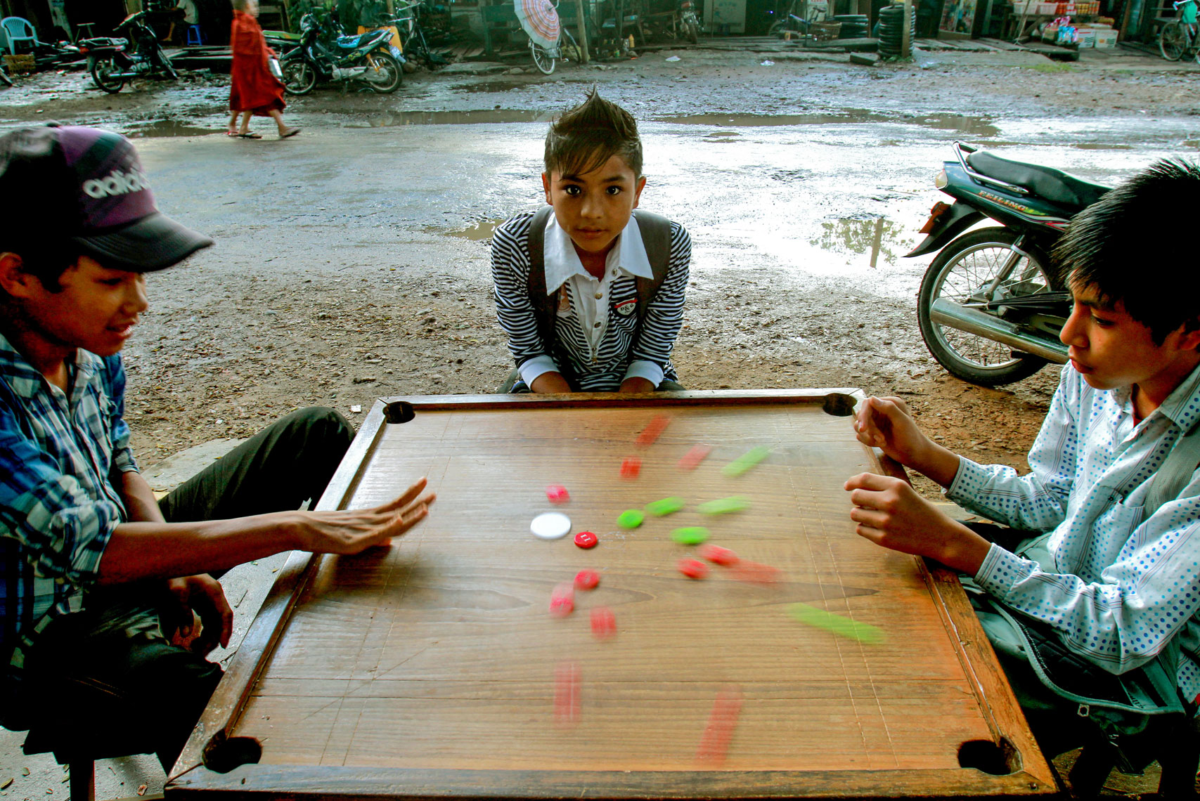 Three boys play carom in the street